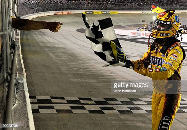 NASCAR official gives the checkered flag to Kyle Busch driver of the MM's Toyota on track after winning the NASCAR Sprint Cup Series Sharpie 500 at...