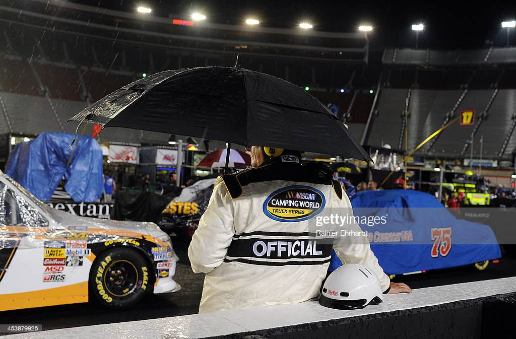 A NASCAR official holds an umbrella as rain falls before the NASCAR Camping World Truck Series UNOH 200 presented by ZLOOP at Bristol Motor Speedway on August 20, 2014 in Bristol, Tennessee.