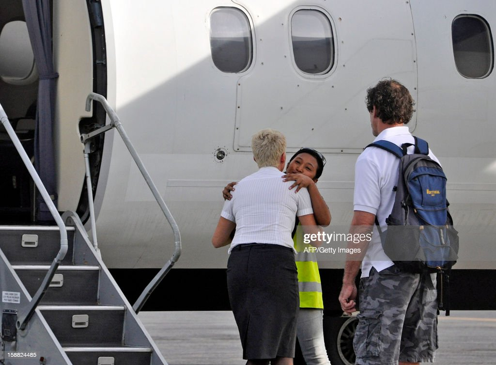 A UN official hugs an East Timorese local UN employee before getting on her plane to leave at Dili's airport on December 31 2012 ahead of the closure...