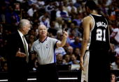Official Joe Crawford talks with head coach Gregg Popovich as Tim Duncan watches from the court in the first half against the San Antonio Spurs of...