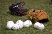 Official major league baseballs lay on the grass next to two gloves prior to the game between the Cleveland Indians and the New York Yankees on...