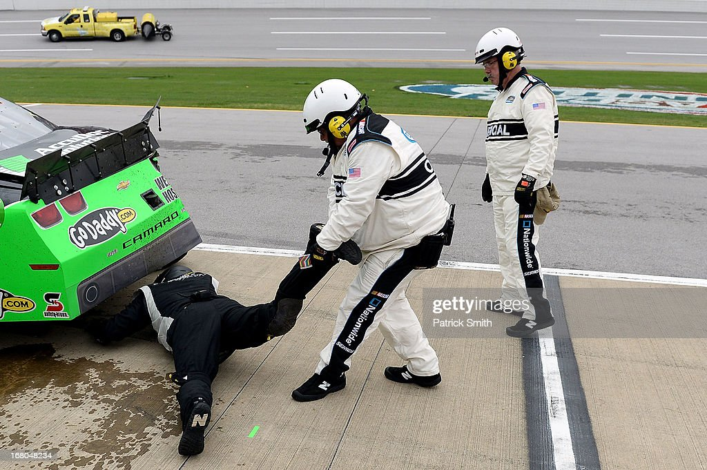 A NASCAR official pulls a crew member the #34 AccuDoc Solutions / GoDaddy Chevrolet driven by Danica Patrick (not pictured) out from under the car due to a safety concern as the crew member was inspecting damage on the car in the pits during the NASCAR Nationwide Series Aaron's 312 at Talladega Superspeedway on May 4, 2013 in Talladega, Alabama.