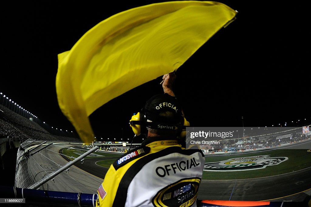 NASCAR official Rodney Wise waves the yellow caution flag near the end of the NASCAR Sprint Cup Series Quaker State 400 at Kentucky Speedway on July 9, 2011 in Sparta, Kentucky.
