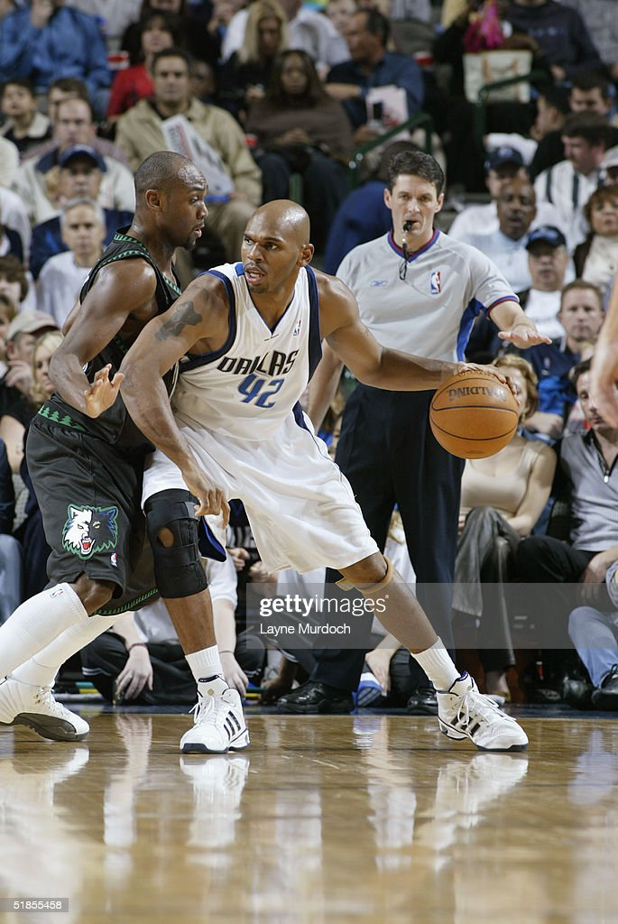 Official Scott Foster watches as Jerry Stackhouse of the Dallas Mavericks is defended by Trenton Hassell of the Minnesota Timberwolves during the...
