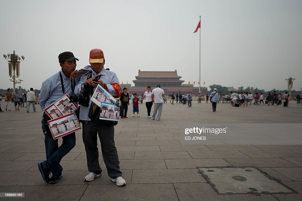 Official tourist photographers stand on Tiananmen square in Beijing on June 4, 2013. Authorities launch a major push every June 4 to prevent discussion of the violently crushed 1989 pro-democracy protests, in which at least hundreds of people died. AFP PHOTO / Ed Jones