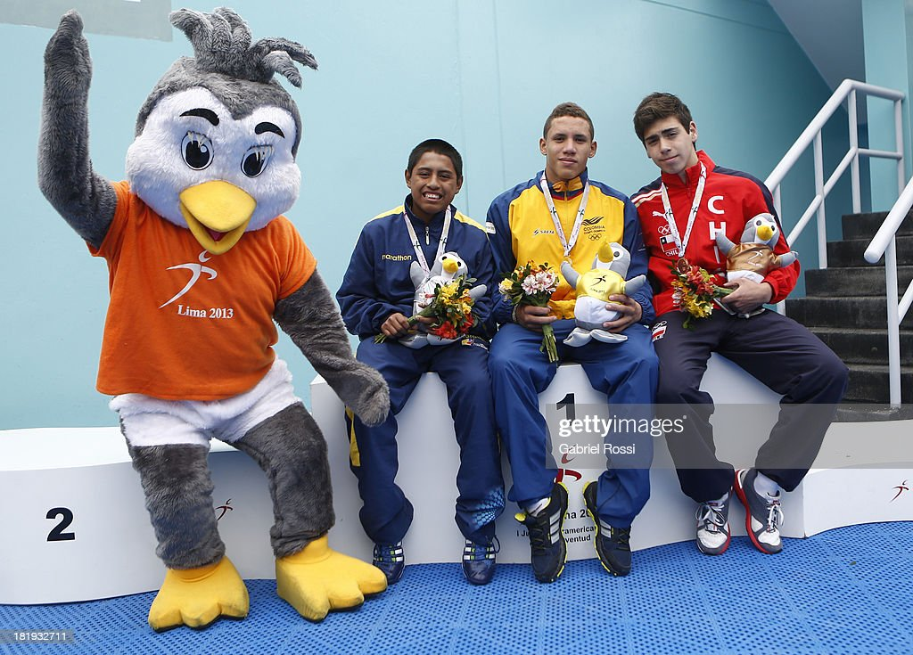 Official tournament mascot, Walter Vera of Ecuator, Alejandro Arias Muñ–oz of Colombia and Vladimir Badilla of Chile pose for a photo after winning the Men's 3m Springboard Diving Final round as part of the I ODESUR South American Youth Games at Villa Deportiva del Callao on September 26, 2013 in Lima, Peru.