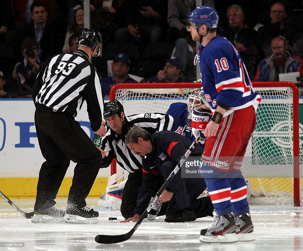 Officials and a member of the ice work fix a hole in the ice as the New York Rangers host the Washington Capitals in Game Two of the Eastern Conference Semifinals during the 2012 NHL Stanley Cup Playoffs at Madison Square Garden on April 30, 2012 in New York City.