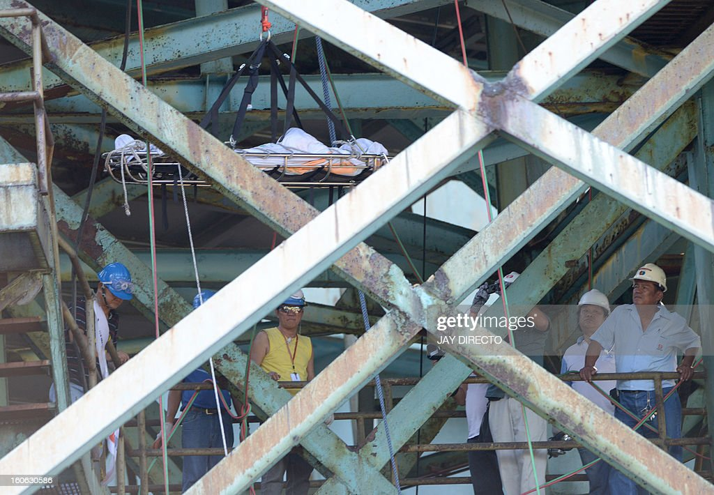 Officials and engineers of the power plant look at a body being lowered by Philippine Red Cross workers that was retrieve from the smokestack after an accident at a power plant in Manila on February 4, 2013. Five workers were killed and dozen injured when scaffolding collapsed while they were repairing a smokestack, according to rescuers. AFP PHOTO / Jay DIRECTO