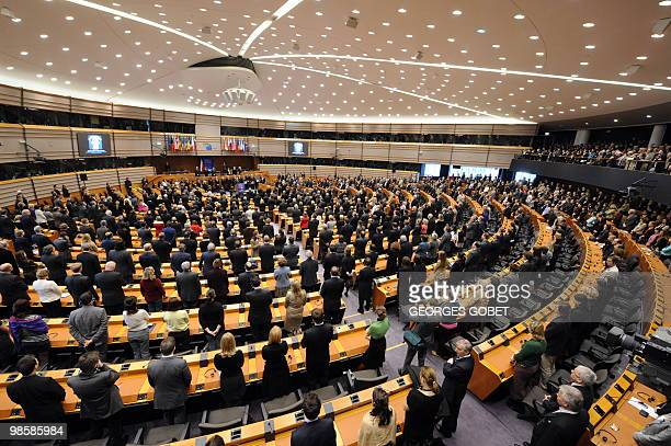 Officials and members of the European Parliament stand in the hemicycle during a special commemorative ceremony on April 14 2010 at the European...