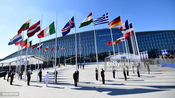 TOPSHOT Officials and military personel stand beneath flags as they attend the NATO summit ceremony at the NATO headquarters in Brussels on May 25...