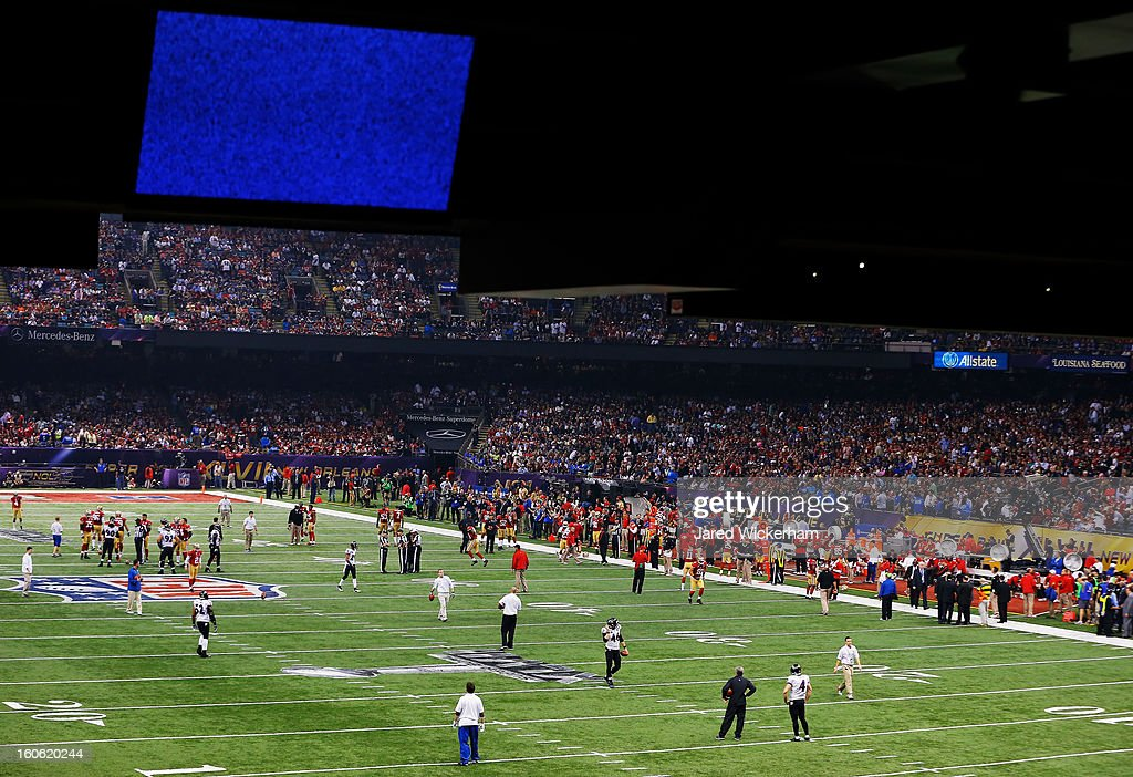Officials and players gather on the field during a power outage during Super Bowl XLVII at the Mercedes-Benz Superdome on February 3, 2013 in New Orleans, Louisiana.