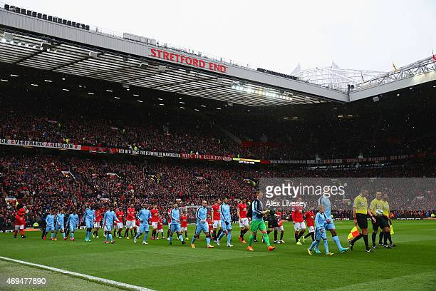 Officials and players walk on to the pitch prior to the Barclays Premier League match between Manchester United and Manchester City at Old Trafford...