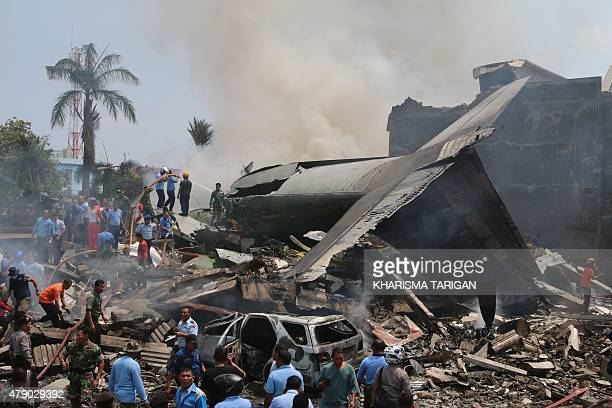 Officials and rescue personnel work at the scene where an Indonesian military C130 Hercules crashed into a residential area in Medan on June 30 2015...