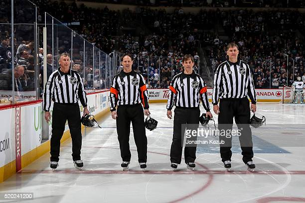Officials Brad Lazarowich Chris Lee Wes McCauley and Shane Heyer stand on the ice prior to puck drop between the Winnipeg Jets and the Minnesota Wild...