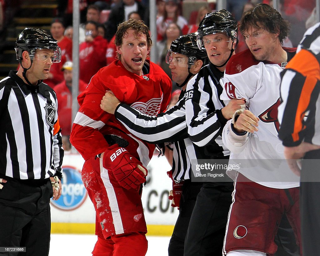 Officials break up a fight between <a gi-track='captionPersonalityLinkClicked' href=/galleries/search?phrase=Justin+Abdelkader&family=editorial&specificpeople=2271858 ng-click='$event.stopPropagation()'>Justin Abdelkader</a> #8 of the Detroit Red Wings and <a gi-track='captionPersonalityLinkClicked' href=/galleries/search?phrase=Shane+Doan&family=editorial&specificpeople=201614 ng-click='$event.stopPropagation()'>Shane Doan</a> #19 of the Phoenix Coyotes during a NHL game at Joe Louis Arena on April 22, 2013 in Detroit, Michigan. Detroit defeated Phoenix 4-0
