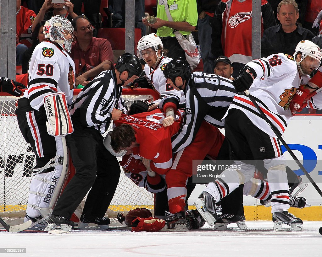 Officials break up a scrum between Henrik Zetterberg #40 of the Detroit Red Wings and Bryan Bickell #29 of the Chicago Blackhawks during Game Four of the Western Conference Semifinals during the 2013 NHL Stanley Cup Playoffs at Joe Louis Arena on May 23, 2013 in Detroit, Michigan.
