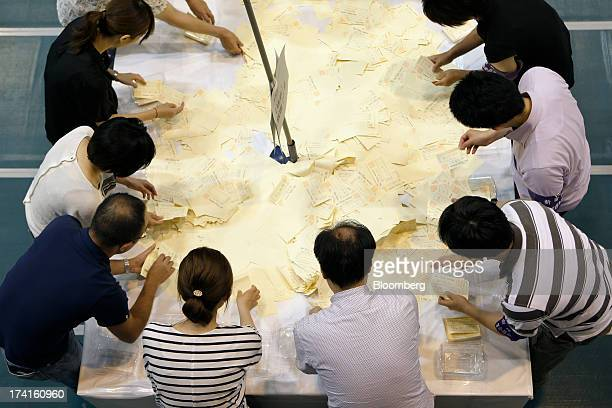 Officials count ballots for the Japanese parliament's upper house election at a ballot counting station in Tokyo Japan on Sunday July 21 2013 Japan's...