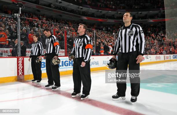 Officials Devin Berg Francois St Laurent Kelly Sutherland and Bryan Pancich stand at center ice for the National Anthem prior to a NHL game between...