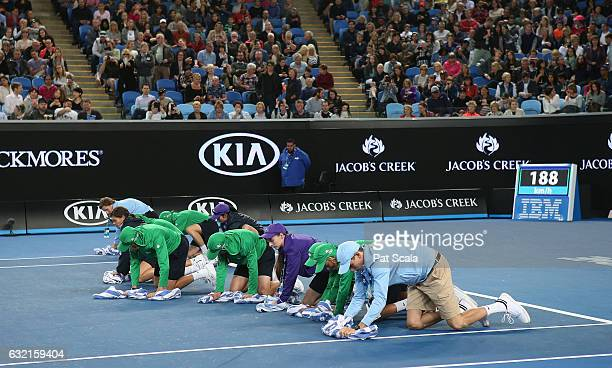 Officials dry the court during a rain delay in the third round match between Kei Nishikori of Japan and Lukas Lacko of Slovakia on day five of the...