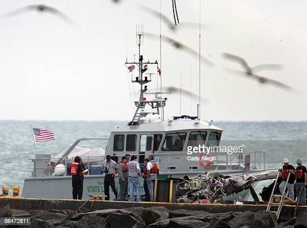 Officials examine an airplane wing on a barge in Govenment Cut after a Chalk's Seaplane burst crashed into the Atlantic Ocean December 20 2005 in...