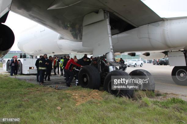 Officials examine the Airbus A340 passenger plane that skidded off the runway at the Ataturk International Airport in Istanbul Turkey on April 22...