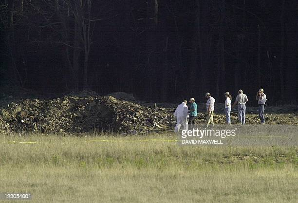 Officials examine the crater 11 September 2001 at the crash site of United Airlines Flight 93 in Shanksville Pennsylvania The plane from Newark New...