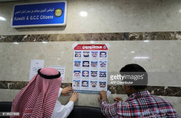 Officials from Kuwait's interior ministry put up a poster on July 20 2017 in a Citizen Service Centre in Kuwait City of fugitives convicted of...