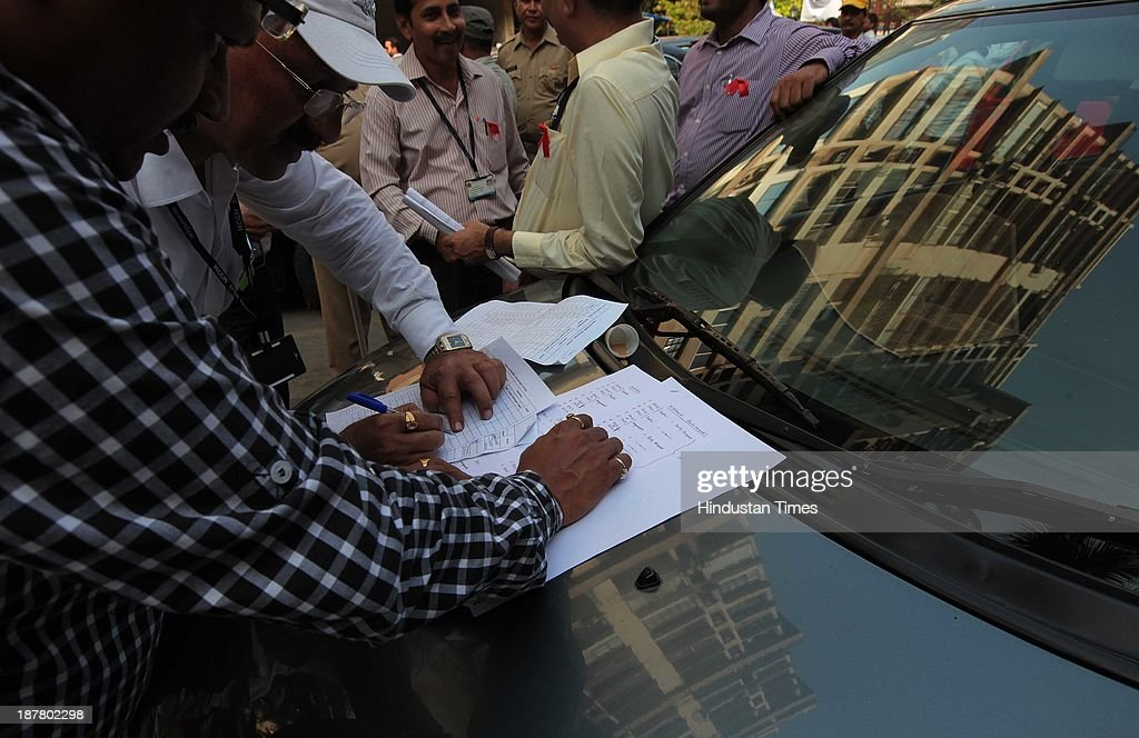 Officials from the BMC building and proposal department scrutinize documents before beginning the demolition process in Campa Cola compound on November 12, 2013 in Mumbai, India. Seven high-rises were constructed at what is called the Campa Cola Compound, between 1981 and 1989. The builders had permission for only five floors, but constructed several more. One of the buildings, Midtown, has 20 floors. Another building, Orchid, has 17. The Supreme Court asked the BMC to investigate, and the civic body served demolition notices for all flats constructed above the fifth floor, which it said were illegal.