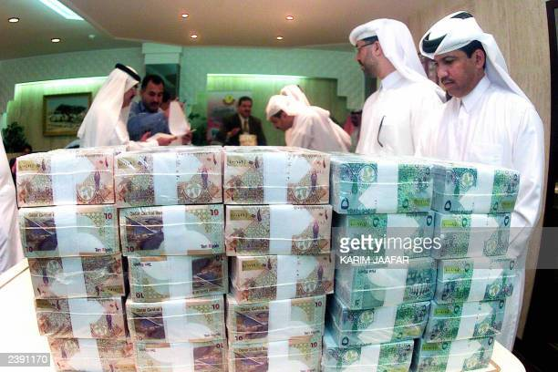 Officials from the Qatar Central Bank hand over new currency notes to the local commercial banks in Doha 15 June 2003 The Qatar Central Bank formally...