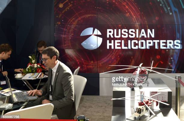 Officials gather beside a model of a helicopter at an aviation stall in the exhibition area on the ithird day of the 11th edition of 'Aero India' a...