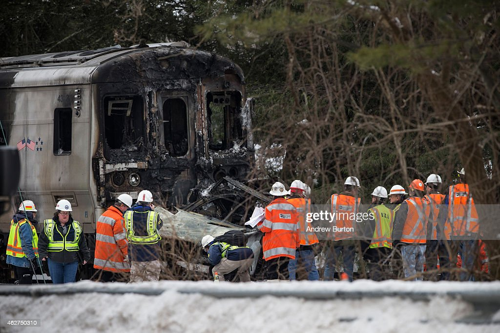 Officials inspect a Metro-North train crash with a sport utility vehicle that occured last night on February 4, 2015 in Valhalla, New York. The crash started a fire in the train cars that killed six people, including the driver of the vehicle.