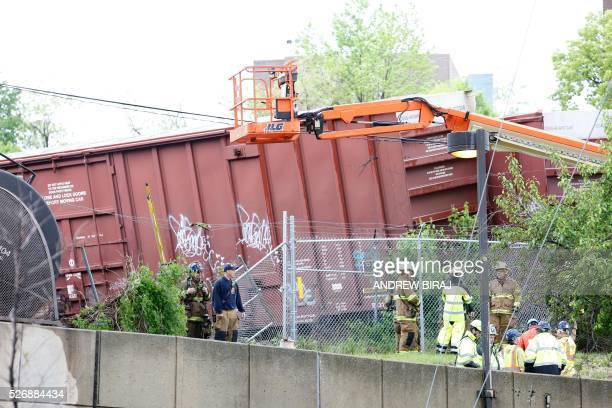 Officials inspect derailed cars at the scene of CSX freight train derailment near the Rhode Island Avenue metro station in Washington DC on May 1...