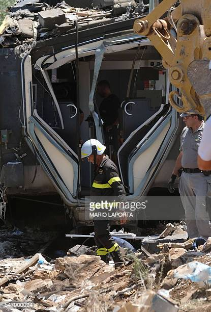 Officials inspect the train crash site on July 13 2016 near Corato in the southern Italian region of Puglia as rescuers searched for missing bodies...