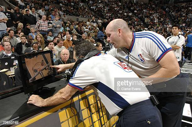 Officials Joe Forte and Gary Zielinski look at instant replay to determine if Fabricio Oberto's basket at the end of the third quarter was good The...