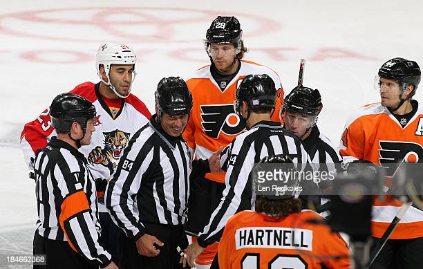 Officials Kelly Sutherland Tony Sericolo Bryan Pancich and Darcy Burchell gather at center ice with Claude Giroux Kimmo Timonen and Scott Hartnell of...