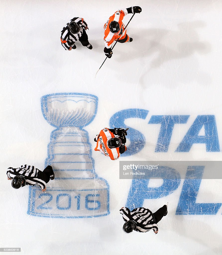 Officials Kevin Pollock Matt MacPherson and Brian Murphy gather with Andrew MacDonald and Matt Read of the Philadelphia Flyers during a stoppage in...
