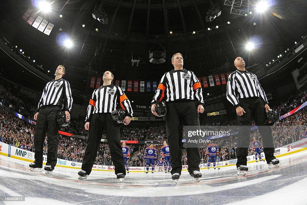 NHL officials line up for the singing of the national anthem prior to a game where the Edmonton Oilers versus the Colorado Avalanche at Rexall Place on January 28, 2013 in Edmonton, Alberta, Canada.