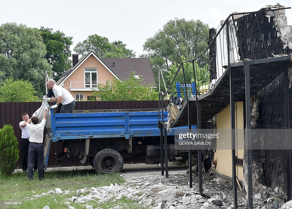 Officials load body bags into a truck at the site of a fire in the village of Litochky, on May 29, 2016. Seventeen people died when a makeshift home for elderly people outside the Ukrainian capital Kiev caught fire in the early hours of May 29, the latest tragedy to shake the conflict-riven country. The fire tore through the two-storey shelter for the elderly which is in the village of Litochky, located some 50 kilometres (31 miles) north of Kiev. / AFP / GENYA