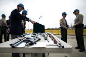 Officials look at confiscated guns prior to the destruction of approximately 3400 guns and other weapons at the Los Angeles County Sheriffs' 22nd...