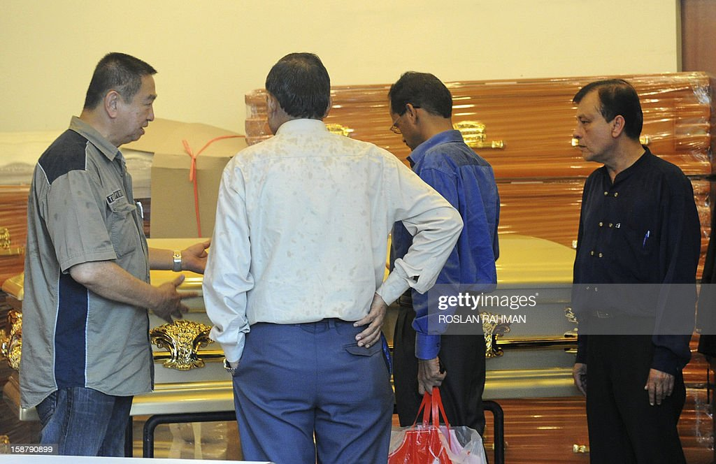 Officials (R) look at the coffin will contain the body of the dead Indian gang-rape victim, at a funeral parlour in Singapore on December 29, 2012 before being fly back to India. The victim, 23, died in Singapore after suffering severe organ failure, the hospital treating her said, in a case that sparked widespread street protests over violence against women.