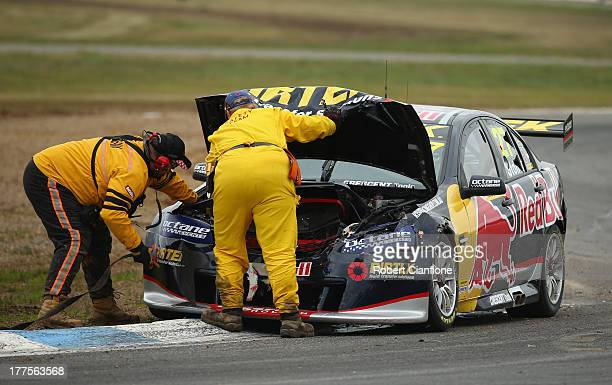 Officials look to remove the Red Bull Pirtek Holden of Casey Stoner from the track after crashing out at the start of race five of the Dunlop...