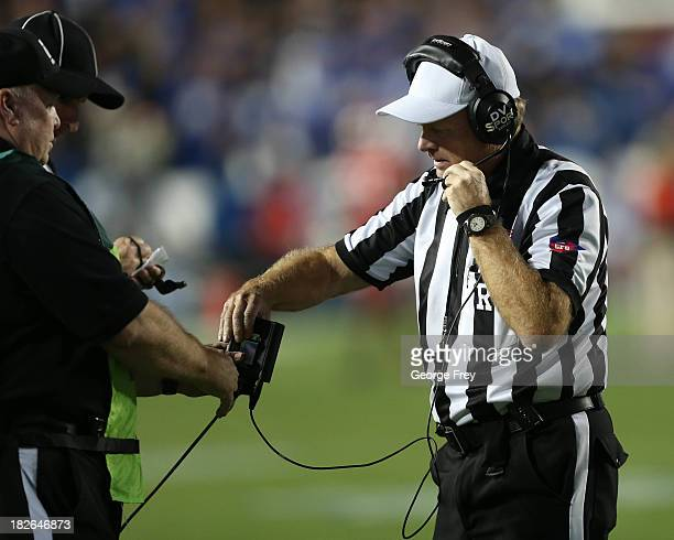 Officials looks at an instant replay during a game between the BYU Cougars and the Utah Utes during the first half of an NCAA football game September...