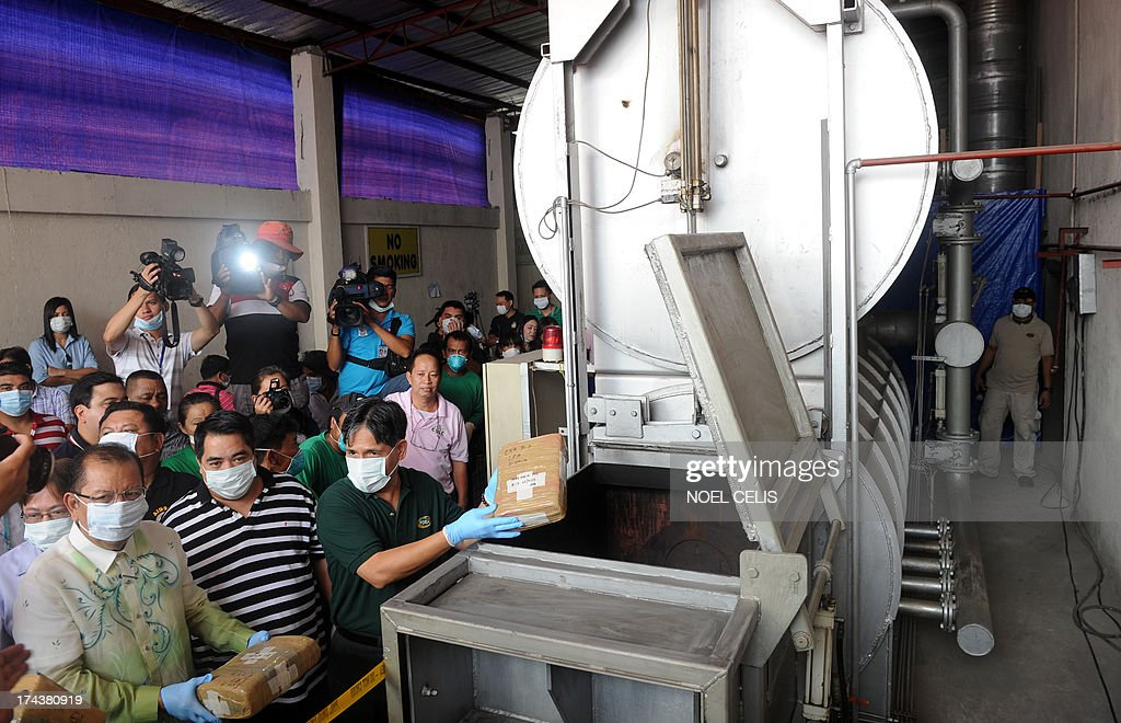 Officials of Philippine Drug Enforcement Agency (PDEA) put seized dangerous drugs into an incinerator in Manila on July 25, 2013. PDEA destroyed 22.33 million USD worth of dangerous drugs composed of methamphetamine hydrochloride, cocaine, marijuana, ecstasy, valium and expired medicines.