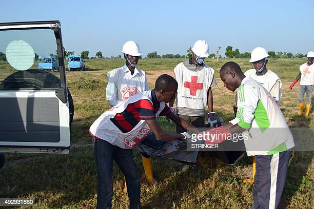 Officials of Red Cross try to remove a dead body at the scene of the blast in Miduguri on October 16 2015 At least 34 people were killed in a wave of...