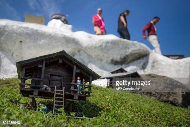 Officials of Swissminiature park walk down above a chalet model at scale after the unveiling ceremony of a new building on July 23 2017 in Melide The...
