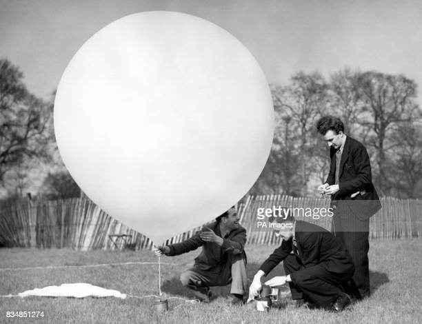 Officials of the Royal Meteorological Society join a radio transmitting device to a balloon to test the weather conditions at 30000 feet above the...