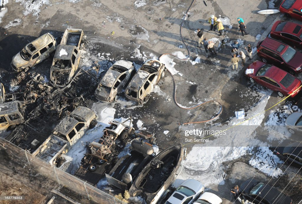 Officials on the scene after a plane crashed into a parking lot area near the Fort Lauderdale Executive Airport in Fort Lauderdale, Florida, on Friday, March 15, 2013.