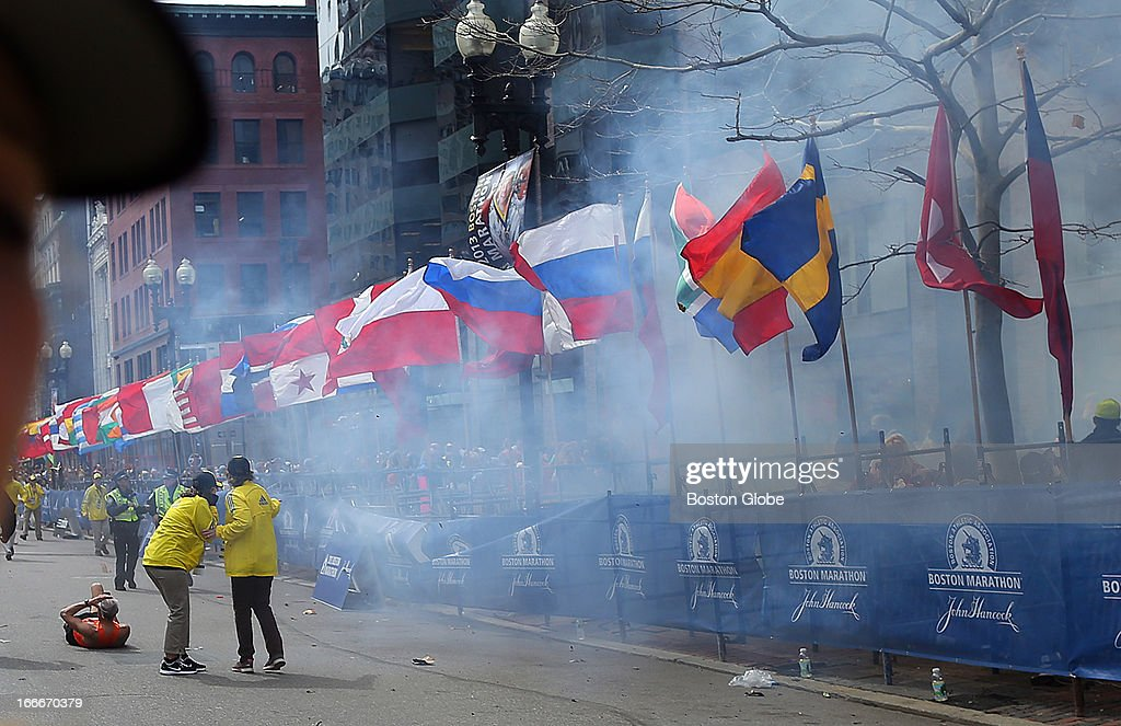 Officials react as the first explosion goes off on Boylston Street near the finish line of the 117th Boston Marathon on April 15, 2013.