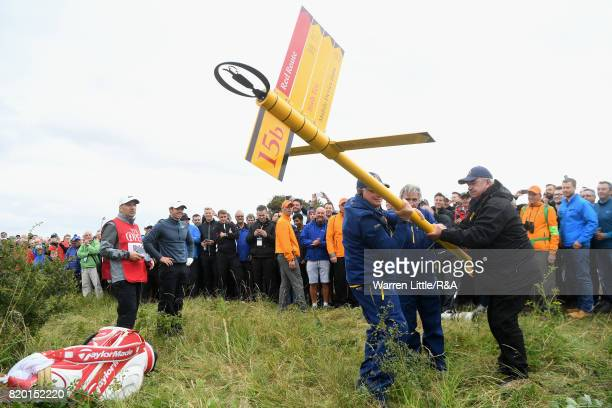 Officials remove a direction sign for Rory McIlroy of Northern Ireland on the 15th hole during the second round of the 146th Open Championship at...