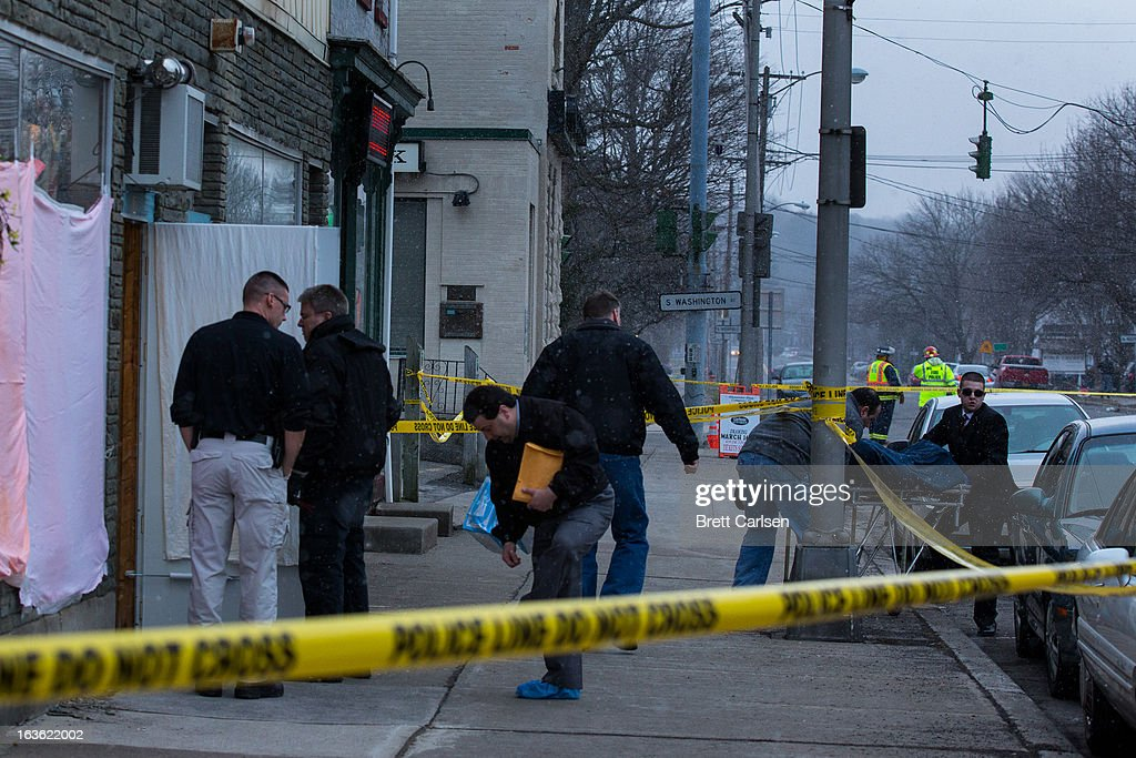 Officials remove the body of a shooting victim from John's Barber Shop as investigators talk outside the doorway on March 13, 2013 in Mohawk, New York. Police have identified 64-year-old Kurt Meyers as a possible suspect responsible for a total of four shooting deaths and two injuries across the area earlier in the day.